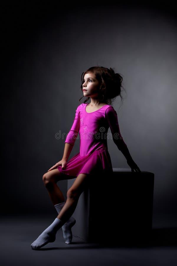 相当节奏性体操运动员坐立方体在演播室 免版税库存照片