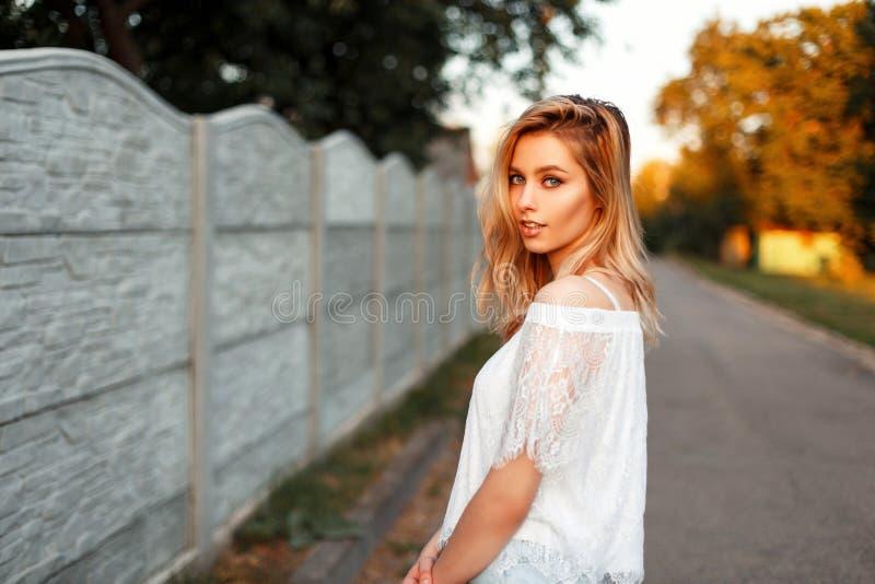 相当葡萄酒T恤杉的白肤金发的愉快的美国妇女 库存图片