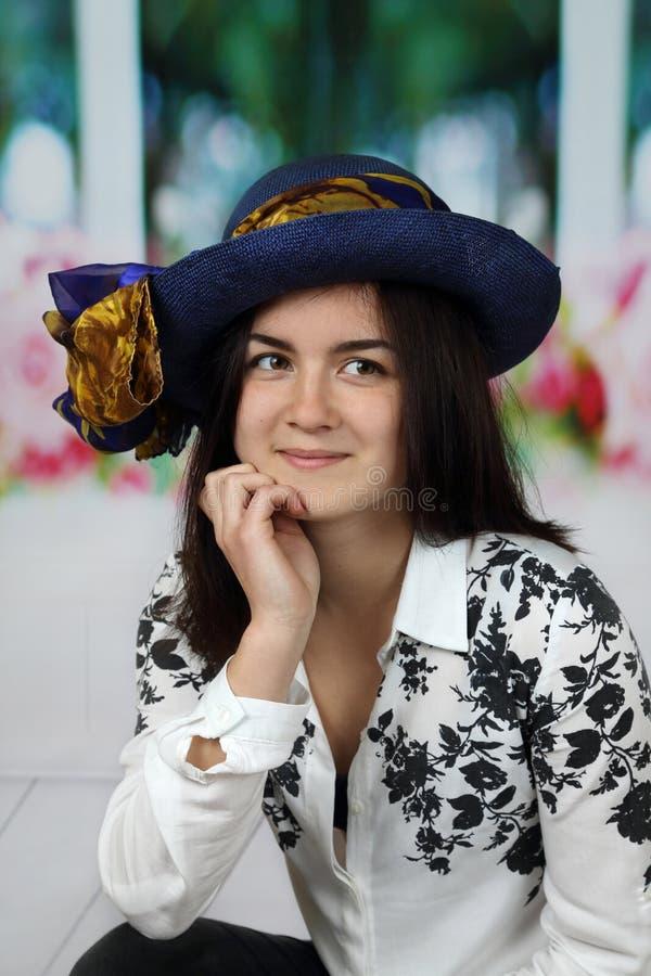 相当蓝色帽子画象的年轻深色的妇女 免版税库存图片