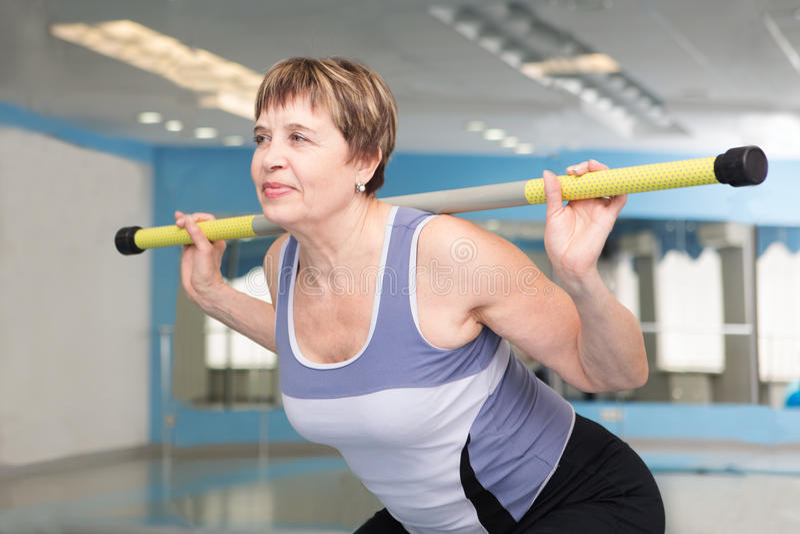 相当行使在健身房的资深妇女 库存图片