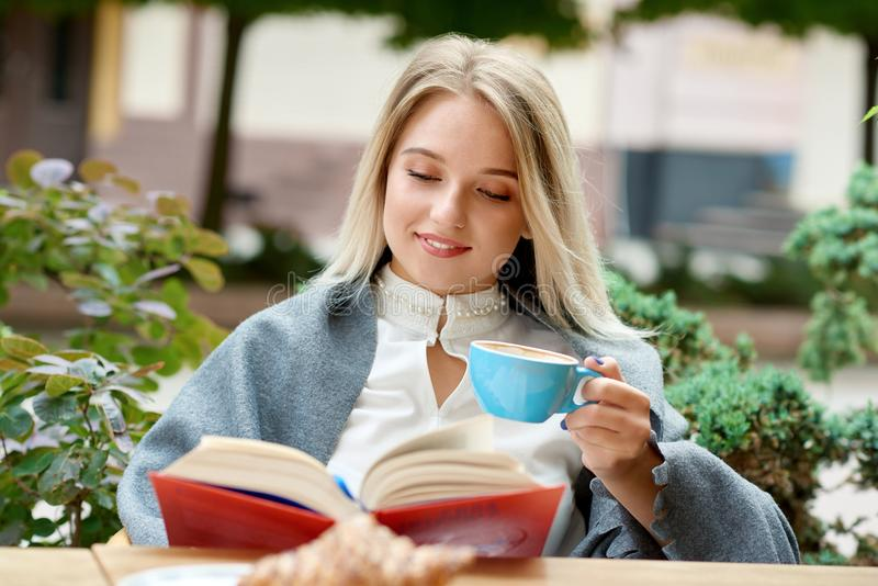 相当读书的白肤金发的女孩坐咖啡馆` s户外休息室 免版税图库摄影