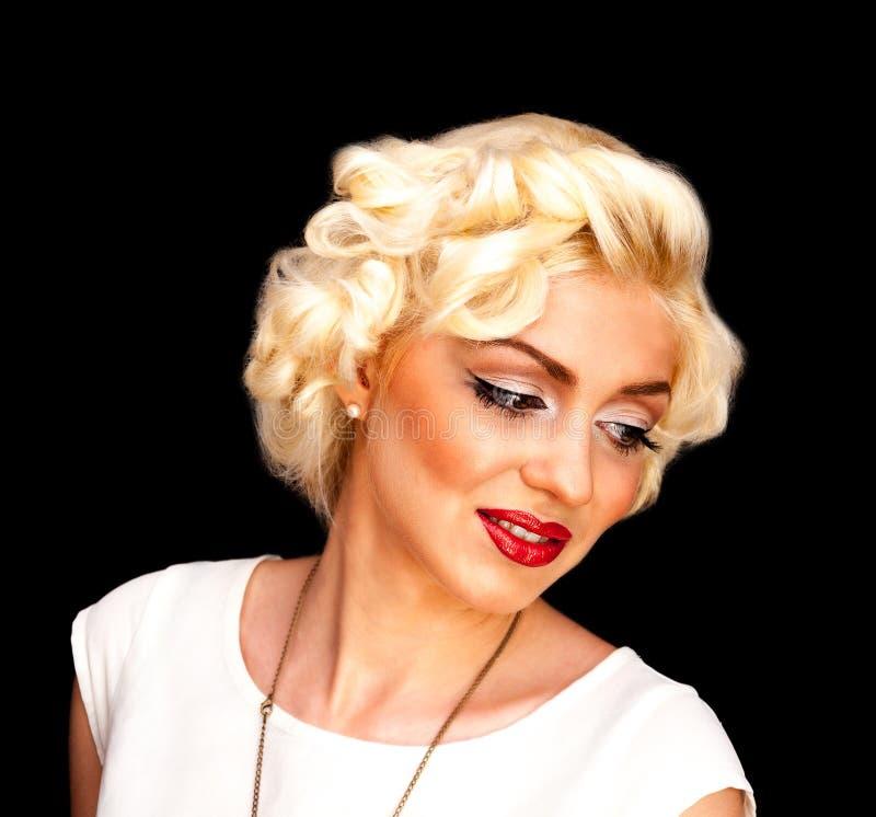 相当象玛丽莲・梦露的白肤金发的女孩模型有红色嘴唇的白色礼服的 免版税图库摄影