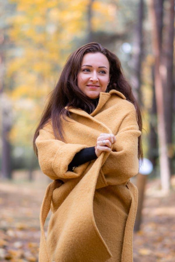 相当走在秋天公园叶子秋天的少妇放松现代休闲的时尚 免版税库存图片