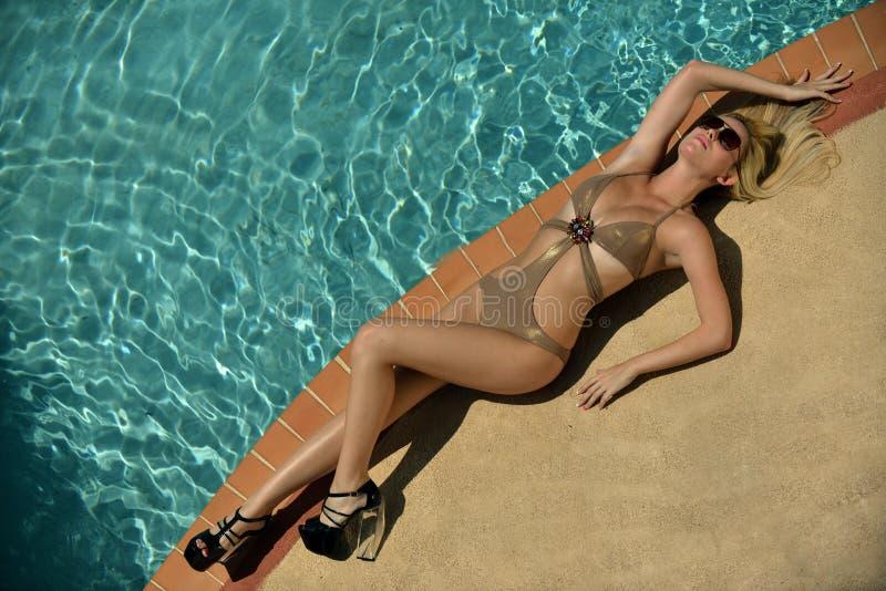 相当躺下在游泳池边缘的白肤金发的模型  图库摄影