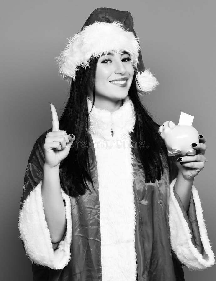 相当逗人喜爱的性感的圣诞老人女孩或微笑的深色的妇女新年毛线衣和圣诞节或者xmas帽子的拿着桃红色贪心猪 库存照片