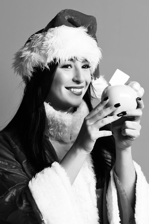相当逗人喜爱的性感的圣诞老人女孩或微笑的深色的妇女新年毛线衣和圣诞节或者xmas帽子的拿着桃红色贪心猪 免版税库存照片