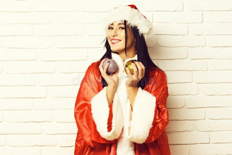 相当逗人喜爱的性感的圣诞老人女孩或微笑的深色的妇女新年毛线衣和帽子的拿着圣诞节或xmas五颜六色的球 免版税库存照片