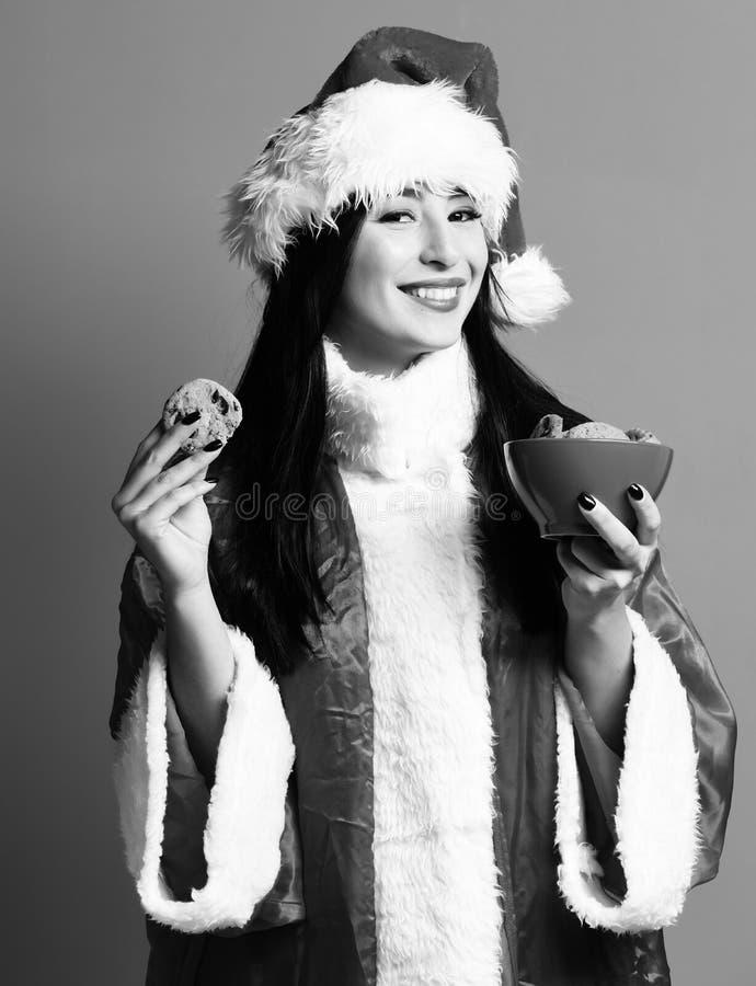 相当逗人喜爱的性感的圣诞老人女孩或微笑的深色的妇女新年毛线衣和帽子的握圣诞节或xmas巧克力臀部 库存照片