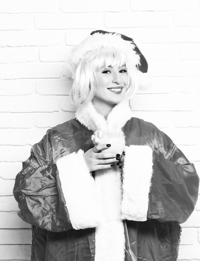 相当逗人喜爱的性感的圣诞老人女孩或微笑的深色的妇女新年红色毛线衣和圣诞节或者xmas帽子的在桃红色假发 库存图片