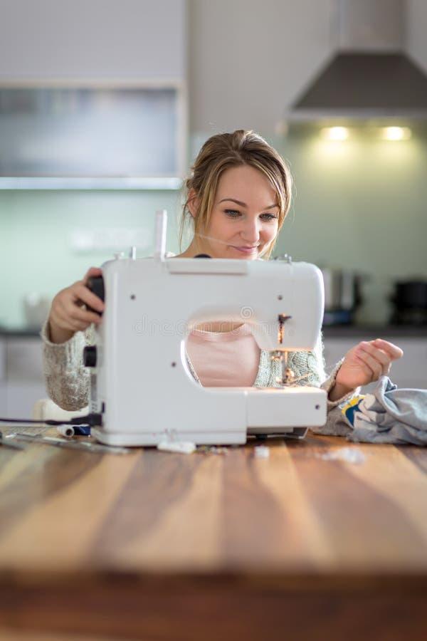 相当,年轻女人缝合的衣裳 免版税库存照片