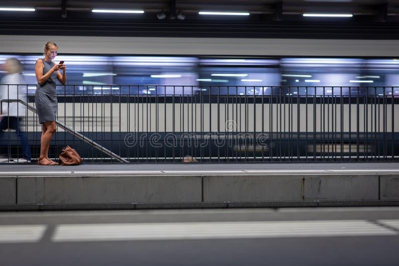 相当,年轻女性通勤者,等待她的火车 免版税库存图片