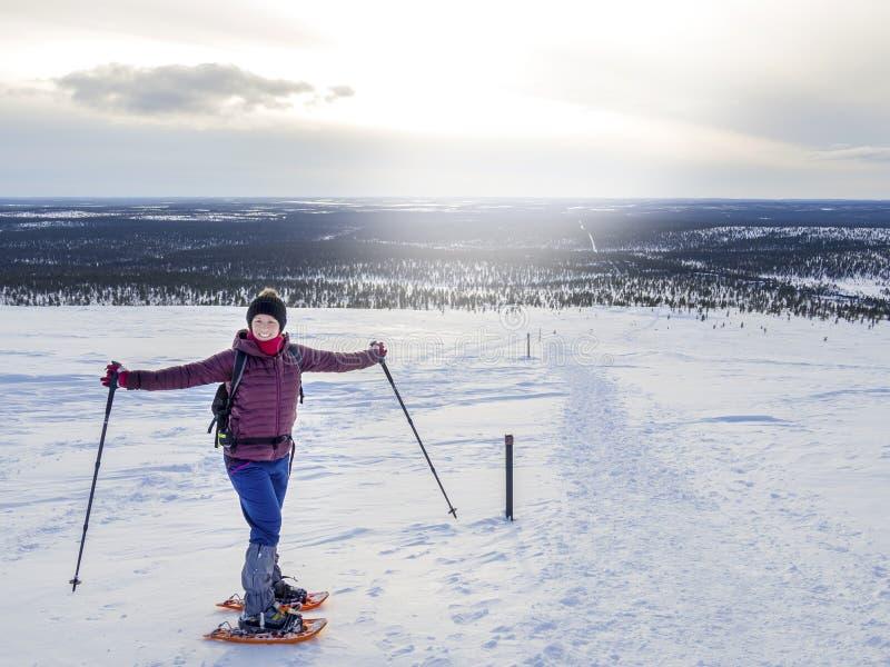 相当,snowshoeing和享用精采冬天wea的年轻女人 免版税库存照片
