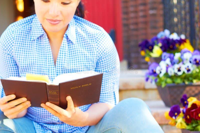 相当读圣经的混合的族种妇女 免版税库存照片