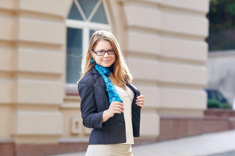 相当戴眼镜的少妇反对街道背景 免版税图库摄影