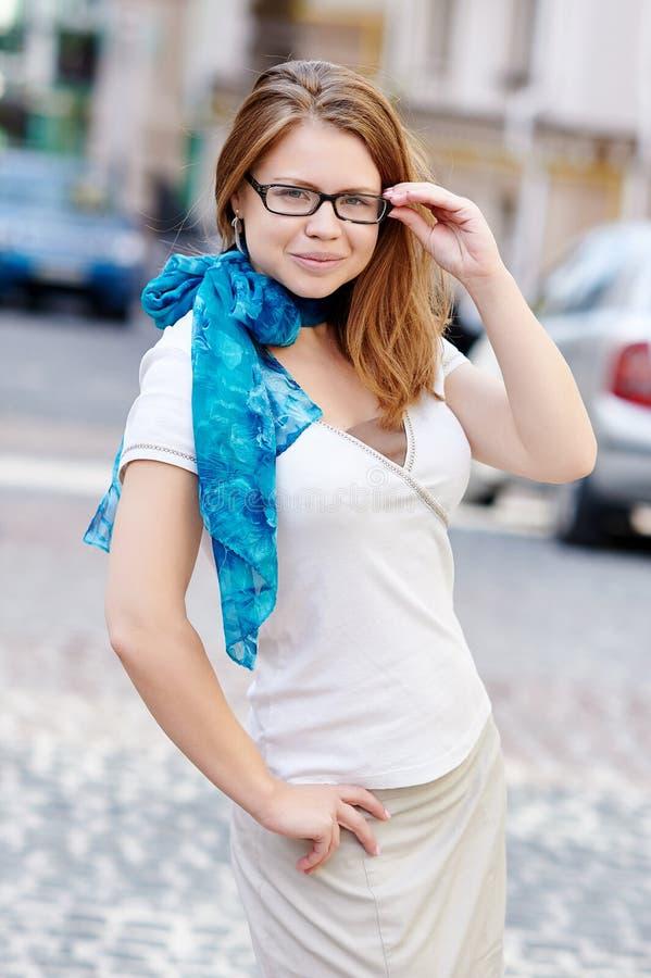 相当戴眼镜的少妇反对街道背景 免版税库存照片