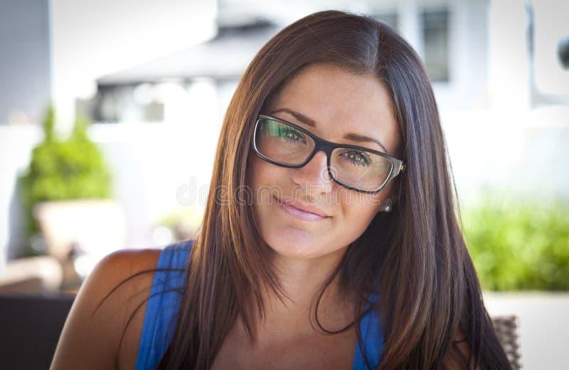 相当戴眼镜的年轻学生妇女 免版税库存照片