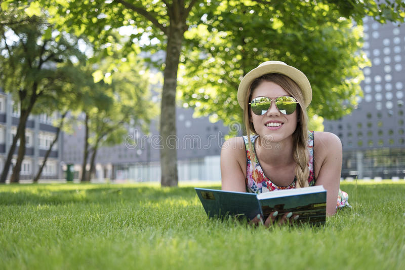 相当说谎在与书的草的少妇 图库摄影