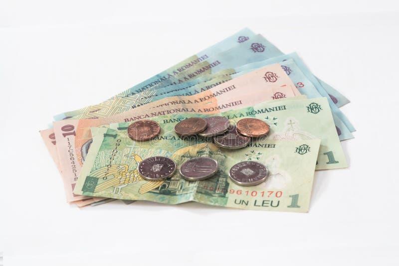相当100, 10和1罗马尼亚人列伊价值的几张钞票与相当10和5罗马尼亚语白色背景的巴尼价值的几枚硬币 库存照片
