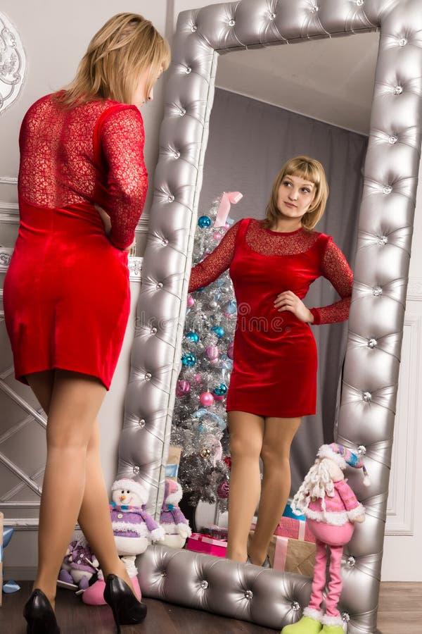 相当stending在墙壁镜子附近的红色礼服的少妇 免版税库存图片