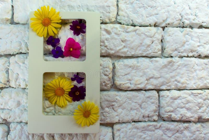 相框和夏天花在内部对kerpich白色墙壁,与花的活图片或垂直的水多的加尔德角 图库摄影