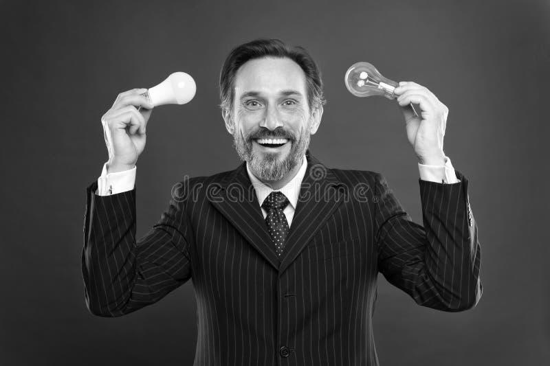 省能源的照明设备 点燃选择存金钱 在红色的人有胡子的顾问正装举行电灯泡 免版税库存图片