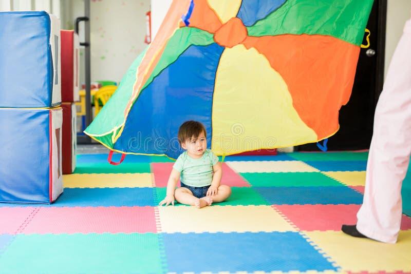 看一个五颜六色的降伞的婴孩 免版税库存照片