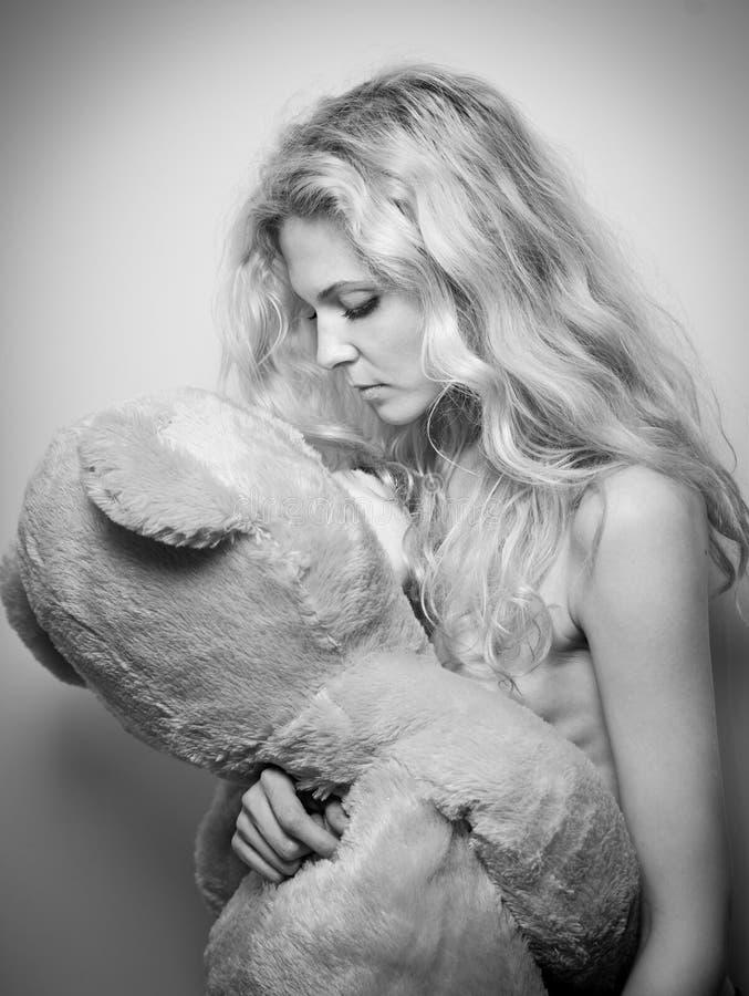 看一个巨大的玩具熊的年轻白肤金发的肉欲的妇女 拿着一个结束大小的玩具的美丽的女孩 舒适场面的可爱的金发碧眼的女人 库存图片
