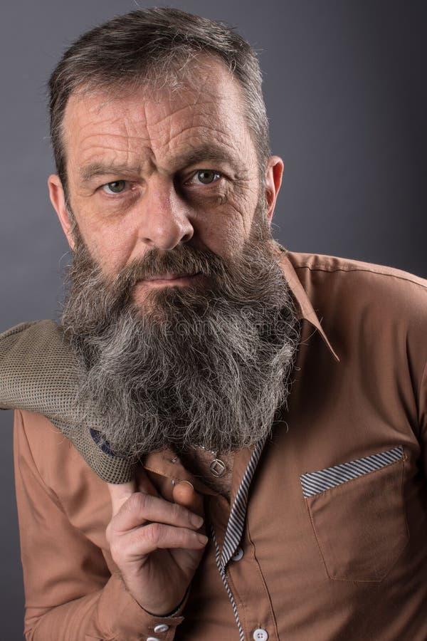 看一个恼怒的脾气坏的老的人的照片非常生气 有长的胡子的男性人在他的面孔 接近面朝上 图库摄影