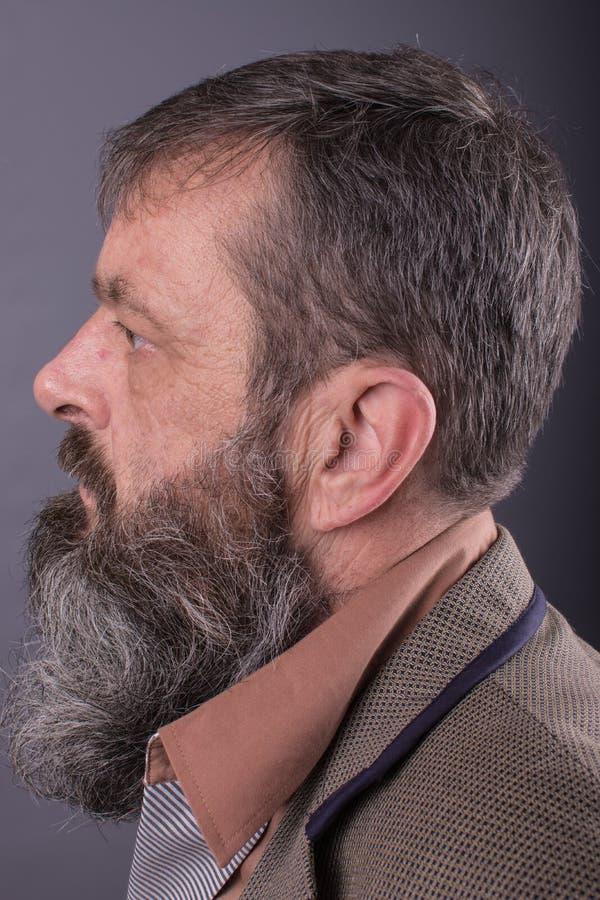看一个恼怒的脾气坏的老的人的照片非常生气 有长的胡子的男性人在他的面孔 接近面朝上 免版税图库摄影
