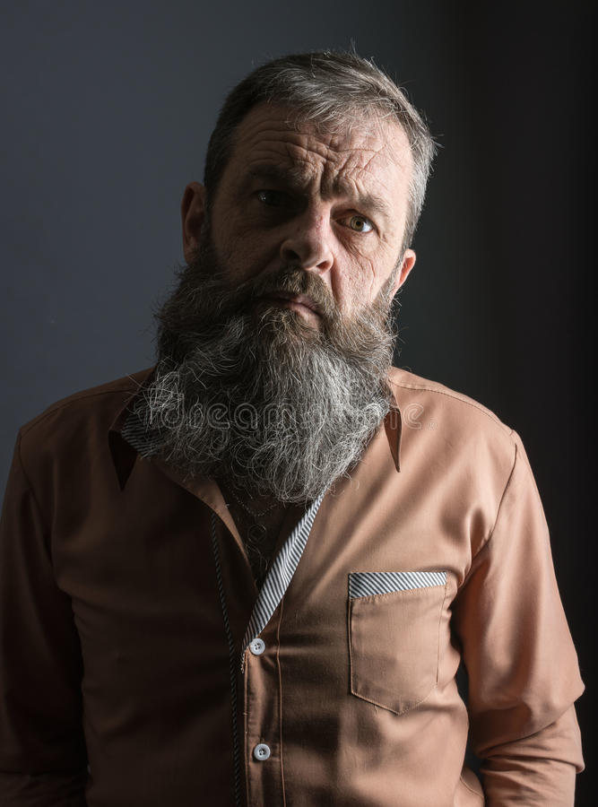 看一个恼怒的脾气坏的老的人的照片非常生气 有长的胡子的男性人在他的面孔 接近面朝上 免版税库存照片