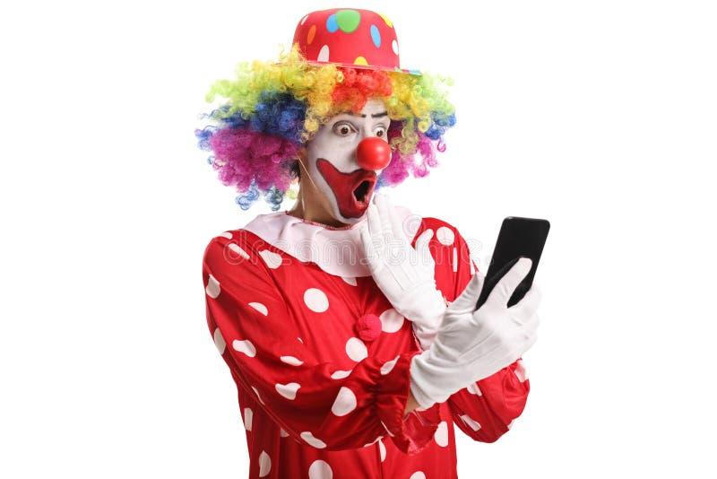 看一个手机的惊奇的小丑 库存图片