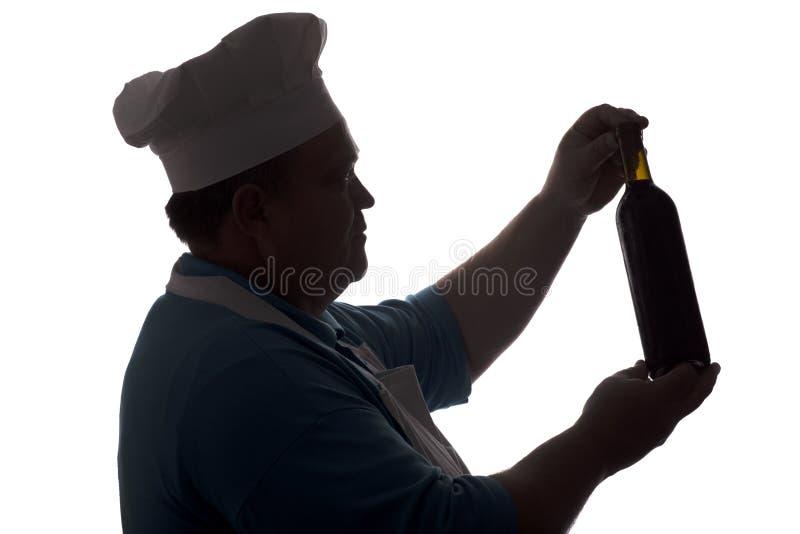 看一个瓶酒和认为在白色被隔绝的背景,一张男性面孔的外形的厨师的剪影在厨师帽子的 免版税库存照片
