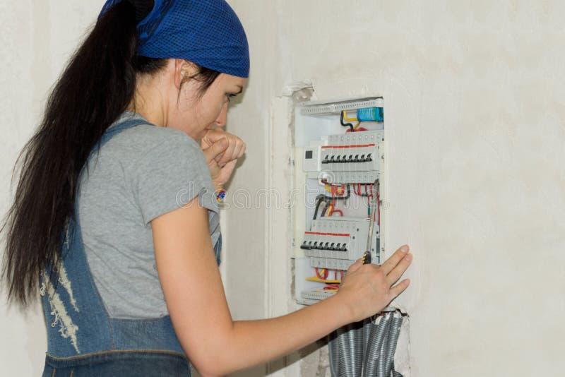 看一个电子保险丝板的妇女 免版税图库摄影