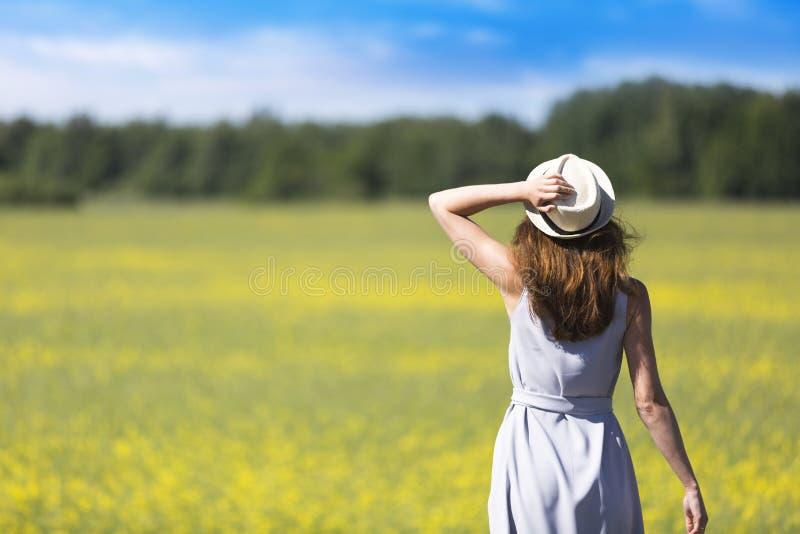 看一个草甸在一个大风天和拿着帽子的美丽的女孩 免版税库存照片