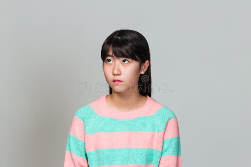 看一名少年东亚的妇女的演播室画象斜向一边 库存照片