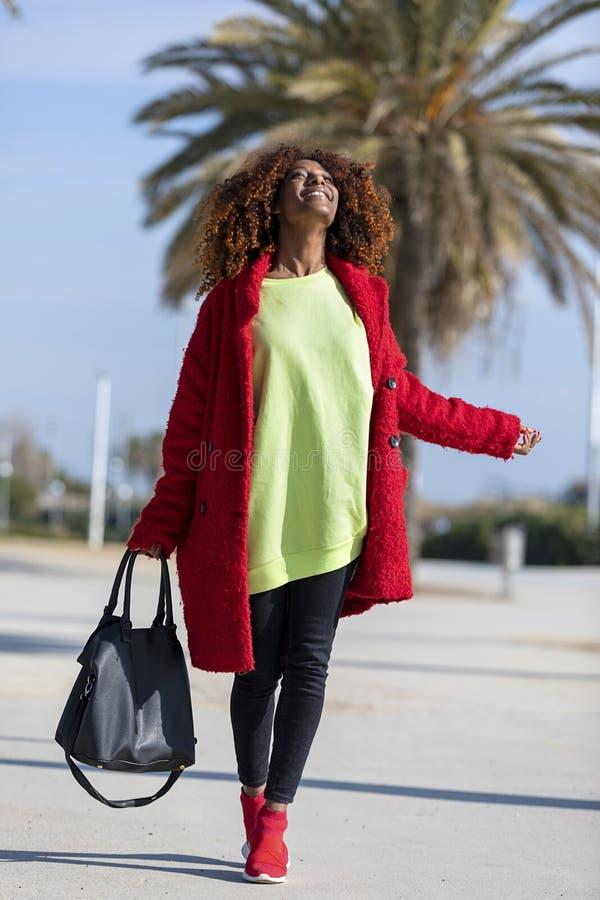 看一名年轻美丽的卷曲非洲的妇女的侧视图微笑和,当站立在城市道路在一好日子时 免版税库存照片