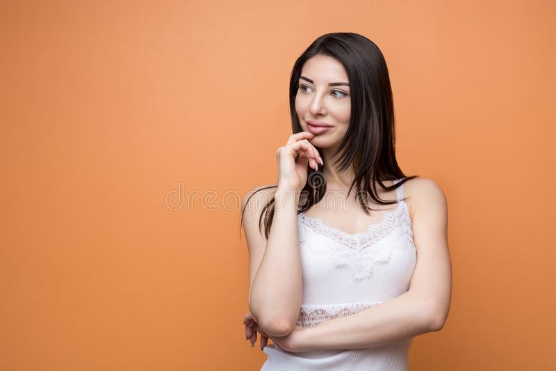 看一名年轻美丽的深色的沉思的妇女的画象握她的手新她的下巴和在旁边 库存图片