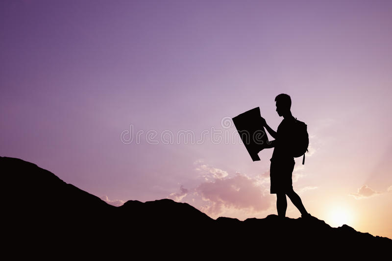 看一张地图本质上的年轻人剪影,当远足时 免版税库存照片