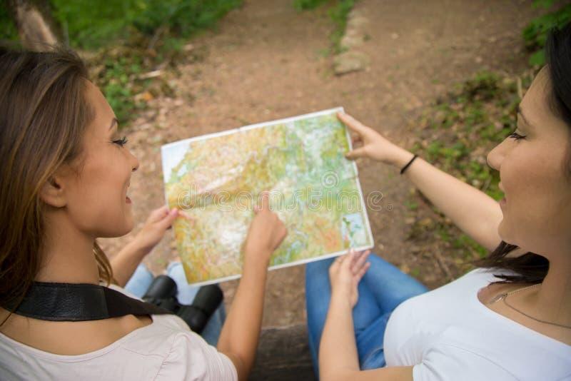 看一张地图的两个女孩在森林里 免版税库存照片