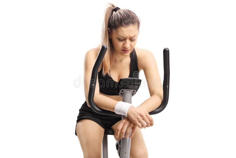 看一辆的锻炼脚踏车的哀伤的年轻女人下来 免版税图库摄影