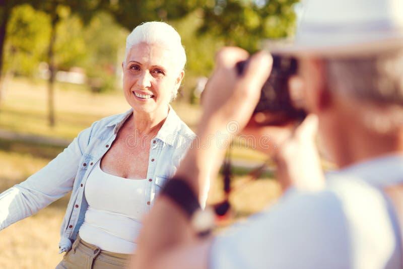 看丈夫的放光的年长妇女拍摄她 库存照片