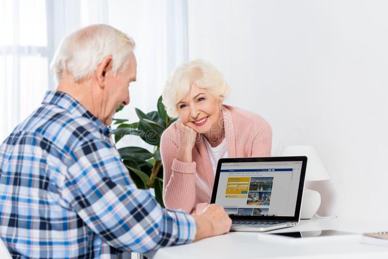 看丈夫的资深妻子画象使用有售票商标的膝上型计算机 库存图片