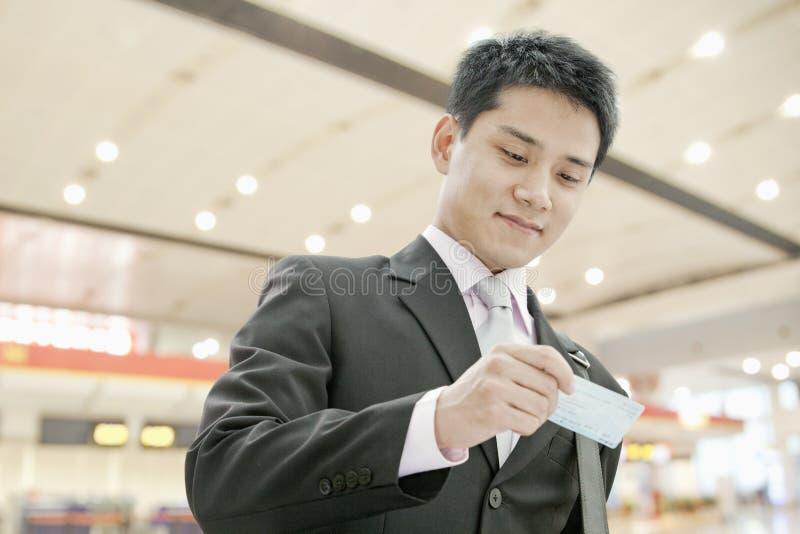 看下来和检查他的票的年轻商人在机场 免版税库存图片