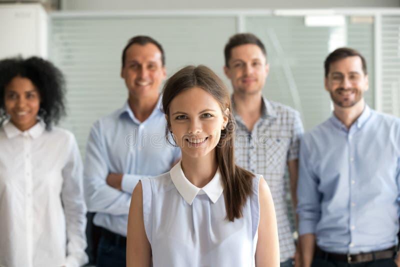 看与不同的队的微笑的女性办公室工作者照相机 库存图片