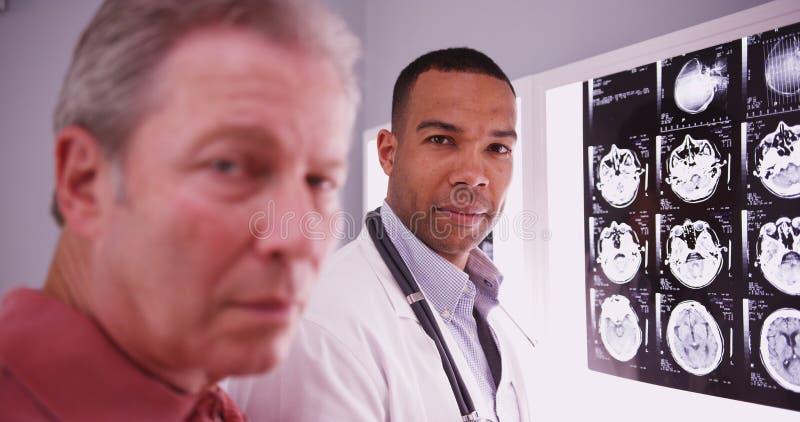 看与中间年迈的患者的年轻聪明的医生照相机 库存照片