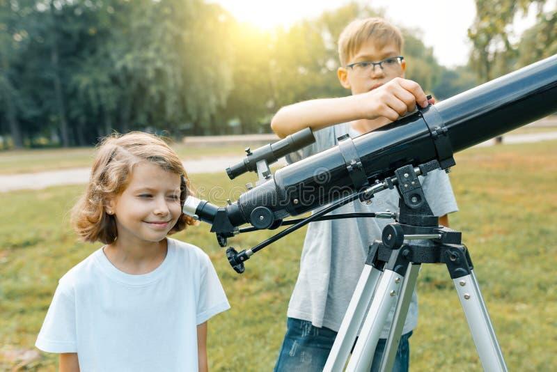 看与兴趣的孩子在望远镜上对天空 免版税图库摄影