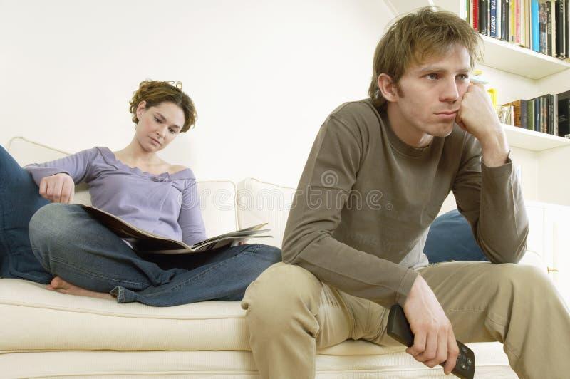 看与妇女读书杂志的人电视 免版税库存图片