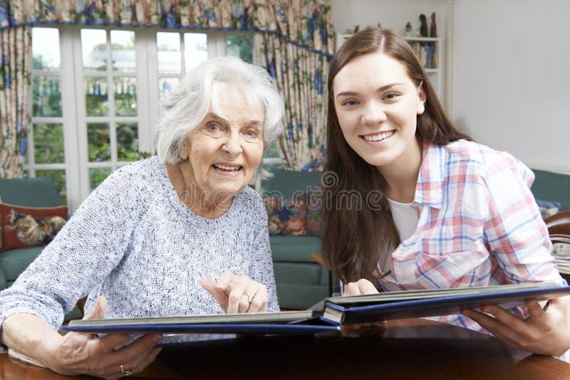 看与少年孙女的祖母象册 免版税图库摄影