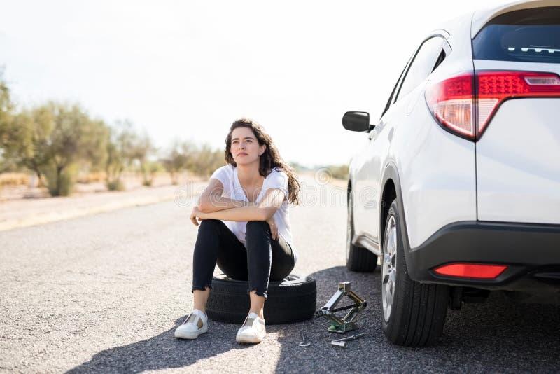 看与平的轮胎的妇女翻倒在她的汽车 免版税图库摄影