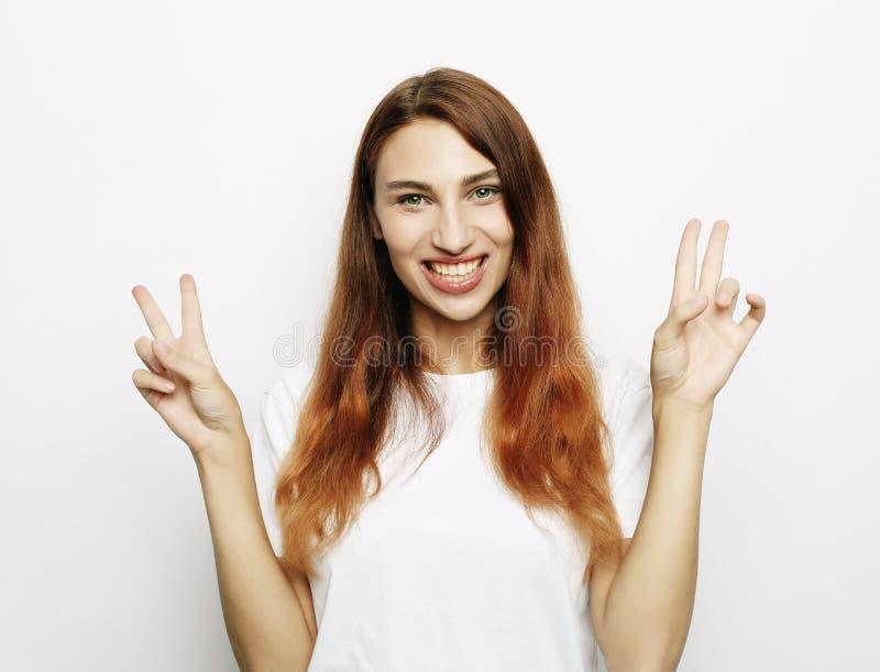 看与微笑的照相机和显示与手指的华美的妇女画象和平标志 库存图片
